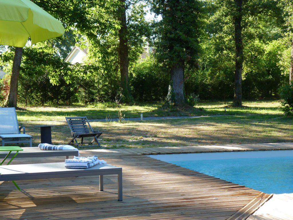 La piscine et sa terrasse avec les gîtes